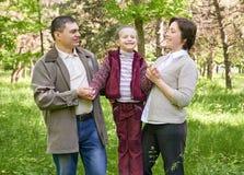 Familia feliz con el niño en parque del verano, luz del sol, hierba verde y árboles Fotos de archivo