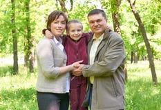 Familia feliz con el niño en parque del verano, luz del sol, hierba verde y árboles Foto de archivo libre de regalías