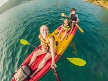 Familia feliz con el niño kayaking en el océano tropical fotos de archivo