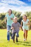 Familia feliz con el niño que corre en el parque Imágenes de archivo libres de regalías