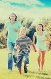 Familia feliz con el niño que corre en el parque Fotografía de archivo libre de regalías