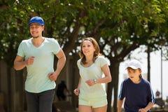 Familia feliz con el niño que corre en parque Foto de archivo libre de regalías
