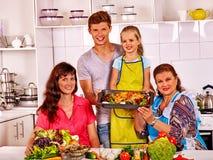 Familia feliz con el niño y el abuelo que cocinan el pollo en la cocina Imágenes de archivo libres de regalías