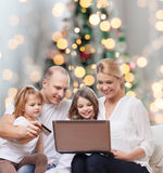Familia feliz con el ordenador portátil y la tarjeta de crédito Imagenes de archivo