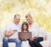Familia feliz con el ordenador portátil y la tarjeta de crédito Fotografía de archivo libre de regalías