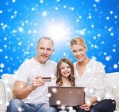 Familia feliz con el ordenador portátil y la tarjeta de crédito Imagen de archivo