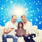 Familia feliz con el ordenador portátil y la tarjeta de crédito Imágenes de archivo libres de regalías