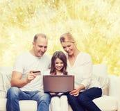 Familia feliz con el ordenador portátil y la tarjeta de crédito Foto de archivo libre de regalías
