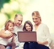 Familia feliz con el ordenador portátil y la tarjeta de crédito Fotos de archivo libres de regalías