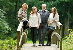 Familia feliz con el padre y las hijas de la madre que se colocan en el puente en el bosque Imagen de archivo libre de regalías