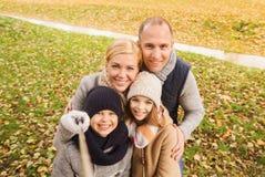 Familia feliz con el palillo del selfie en parque del otoño Fotos de archivo libres de regalías