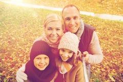 Familia feliz con el palillo del selfie en parque del otoño Imagenes de archivo