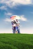 Familia feliz con el paraguas colorido en prado Fotos de archivo libres de regalías