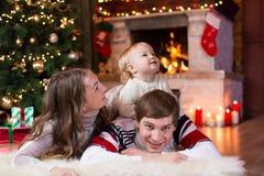Familia feliz con el pequeño hijo que miente cerca de la Navidad Imagen de archivo