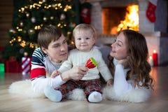 Familia feliz con el pequeño hijo que miente cerca de la Navidad Fotografía de archivo