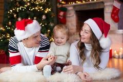 Familia feliz con el pequeño hijo que miente cerca de la Navidad Imágenes de archivo libres de regalías