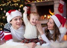 Familia feliz con el pequeño hijo que miente cerca de la Navidad Fotos de archivo libres de regalías