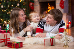 Familia feliz con el pequeño hijo que miente cerca de la Navidad Fotos de archivo