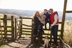 Familia feliz con el perro por una puerta en el campo Fotos de archivo libres de regalías
