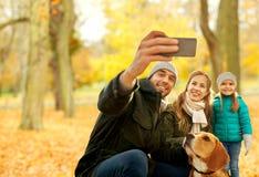 Familia feliz con el perro que toma el selfie en parque del otoño foto de archivo libre de regalías