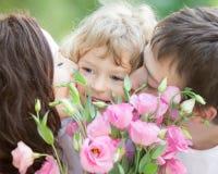 Familia feliz con el ramo de flores de la primavera Foto de archivo libre de regalías