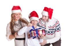 Familia feliz con el rectángulo de regalo. La Navidad. Imágenes de archivo libres de regalías