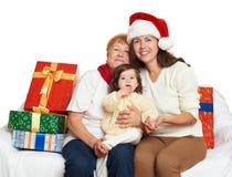 Familia feliz con el regalo de la caja, la mujer con el niño y los ancianos - concepto del día de fiesta Imagen de archivo libre de regalías