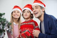 Familia feliz con el regalo de la Navidad que mira lejos Foto de archivo