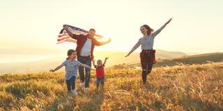 Familia feliz con la bandera de América los E.E.U.U. en la puesta del sol al aire libre fotografía de archivo libre de regalías
