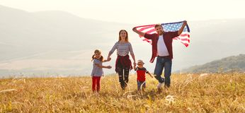 Familia feliz con la bandera de América los E.E.U.U. en la puesta del sol al aire libre fotos de archivo libres de regalías