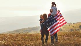 Familia feliz con la bandera de América los E.E.U.U. en la puesta del sol al aire libre imagenes de archivo