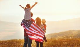 Familia feliz con la bandera de Am?rica los E.E.U.U. en la puesta del sol al aire libre fotografía de archivo