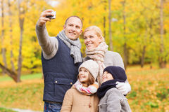Familia feliz con la cámara en parque del otoño Imagenes de archivo