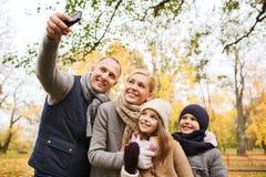 Familia feliz con la cámara en parque del otoño Imagen de archivo