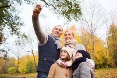 Familia feliz con la cámara en parque del otoño Imágenes de archivo libres de regalías