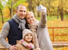 Familia feliz con la cámara en parque del otoño Fotografía de archivo