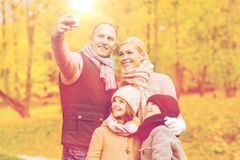 Familia feliz con la cámara en parque del otoño Fotos de archivo