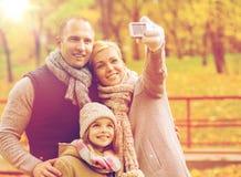 Familia feliz con la cámara en parque del otoño Imagen de archivo libre de regalías