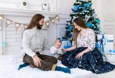 Familia feliz con la caja de regalo que se sienta cerca del árbol de navidad en casa Imágenes de archivo libres de regalías