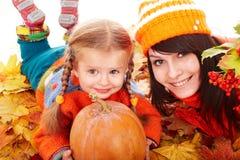 Familia feliz con la calabaza en las hojas de otoño. Fotografía de archivo