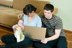 Familia feliz con la computadora portátil Imagen de archivo libre de regalías