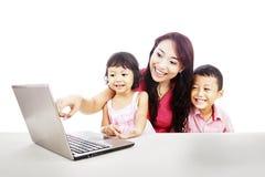 Familia feliz con la computadora portátil del ultrabook Fotos de archivo libres de regalías
