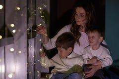 Familia feliz con la guirnalda de la luz de la Navidad Fotos de archivo