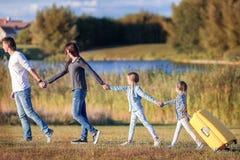 Familia feliz con la maleta que camina al aire libre Imágenes de archivo libres de regalías