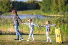 Familia feliz con la maleta que camina al aire libre Foto de archivo libre de regalías