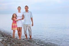 Familia feliz con la muchacha que se coloca en la playa Imagen de archivo libre de regalías