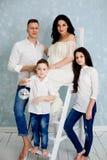 Familia feliz con la mujer embarazada y los niños que presentan en el estudio fotografía de archivo libre de regalías