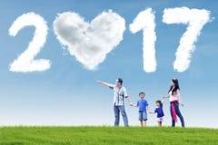 Familia feliz con la nube 2017 en el campo Foto de archivo libre de regalías