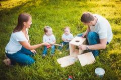 Familia feliz con la pajarera de madera Imagenes de archivo