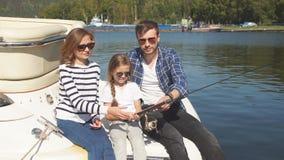 Familia feliz con la pesca de la hija en la charca en caída almacen de metraje de vídeo